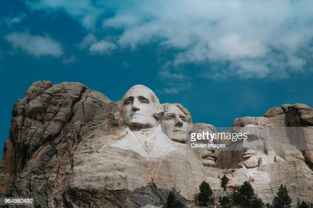 low angle view of mt rushmore national monument against cloudy sky - mt rushmore national monument stock pictures, royalty-free photos & images