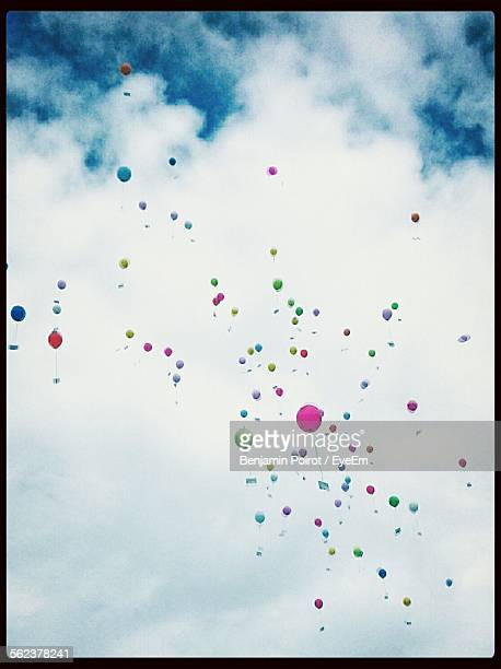 Low Angle View Of Multi Colored Balloons Flying Against Cloudy Sky