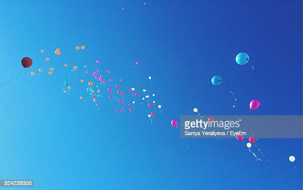 Low Angle View of Multi Colored Balloons Flying In Clear Sky