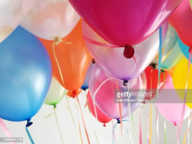 low angle view of multi colored balloons - helium balloon stock pictures, royalty-free photos & images