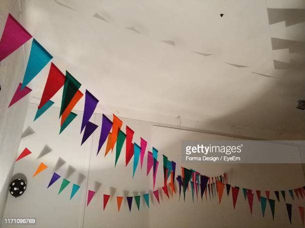 low angle view of multi colored bunting flags hanging from ceiling - forma stock pictures, royalty-free photos & images