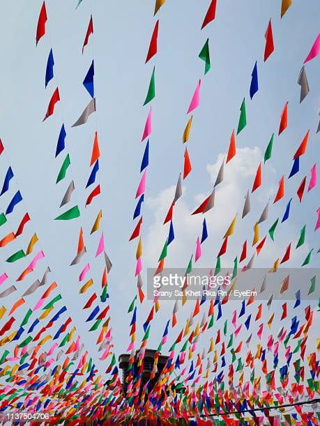 low angle view of multi colored bunting hanging against sky - bunting stock pictures, royalty-free photos & images