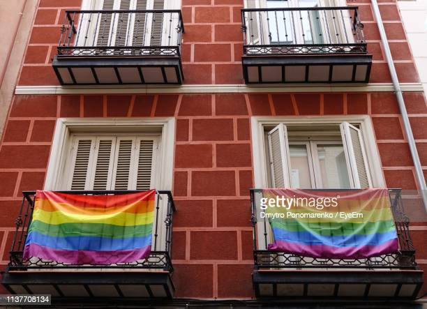 low angle view of multi colored fabrics on building balcony - pride flag stock pictures, royalty-free photos & images