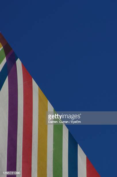 low angle view of multi colored flag against clear blue sky  pride 2020 - curran stock pictures, royalty-free photos & images