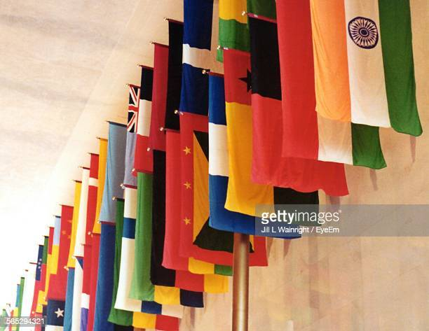 low angle view of multi colored flags hanging on pole - national flag stock photos and pictures