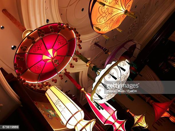 low angle view of multi colored lamps hanging from ceiling - muro stock photos and pictures