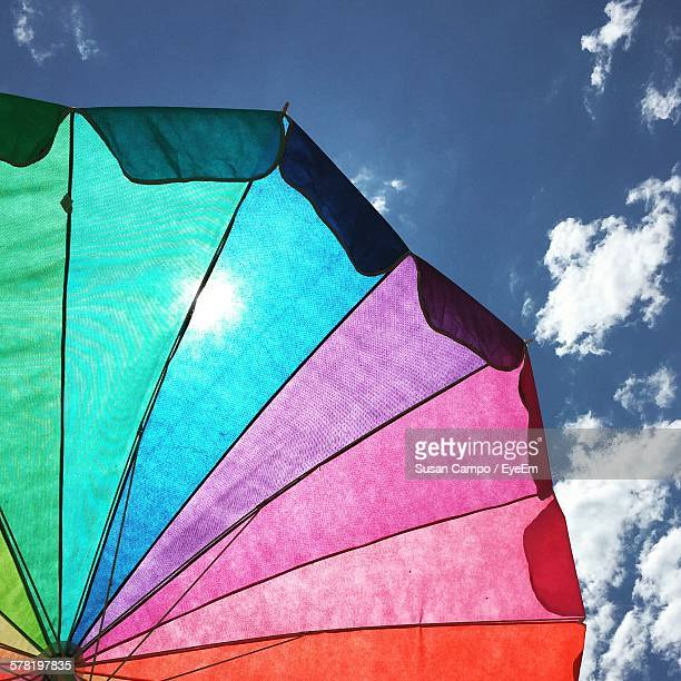 Low Angle View Of Multi Colored Parasol Against Sky On Sunny Day
