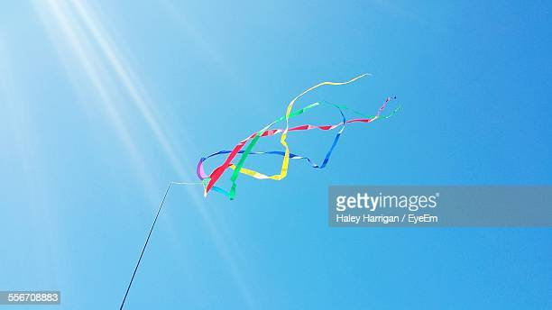 Low Angle View Of Multi Colored Ribbons Attached To Pole Against Clear Blue Sky