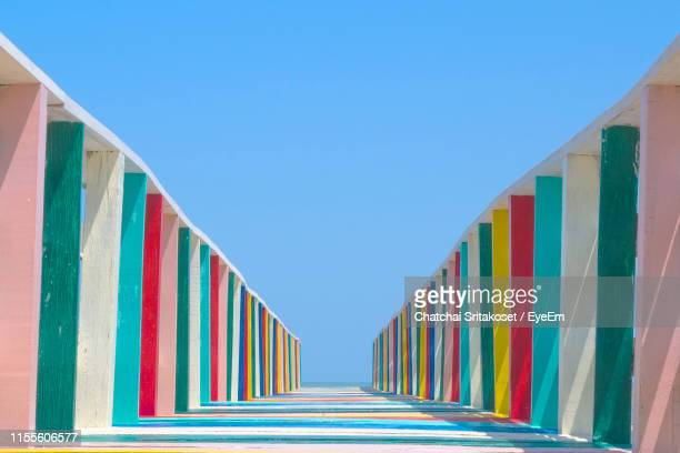 low angle view of multi colored wooden footbridge against sky - clear sky stock pictures, royalty-free photos & images
