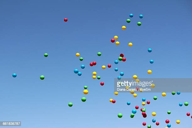 low angle view of multicolor balloons flying against blue sky - 豊富 ストックフォトと画像