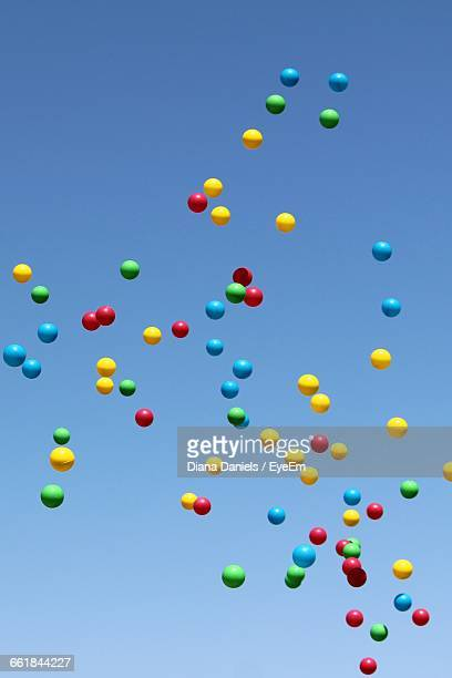 low angle view of multicolor balloons flying against blue sky - diana daniels stock-fotos und bilder