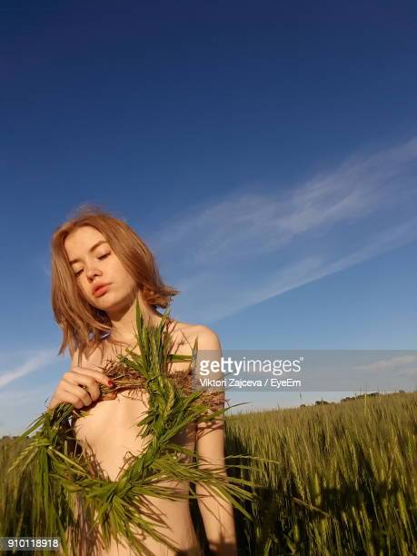 Low Angle View Of Naked Woman Holding Wreath While Standing In Field
