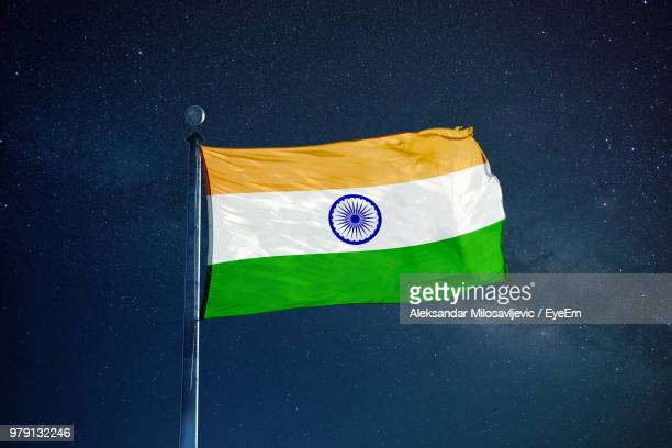 Low Angle View Of National Flag Waving Against Star Field At Night