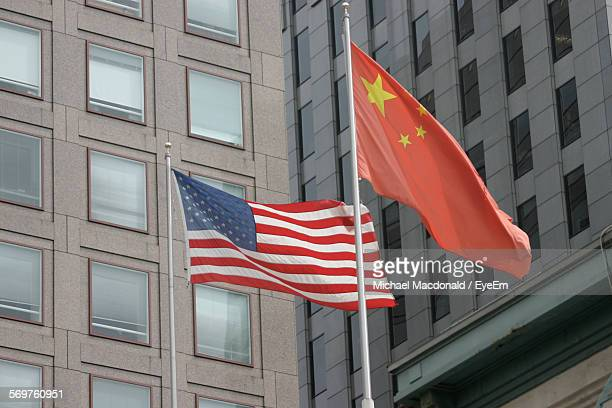 low angle view of national flags against building in city - american stock pictures, royalty-free photos & images