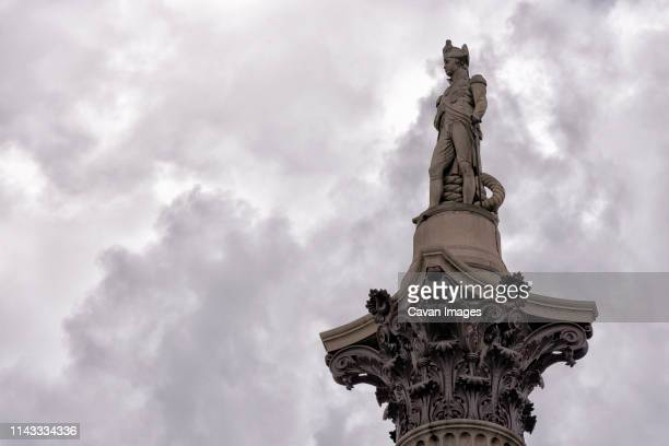 low angle view of nelson's column against cloudy sky - nelson's column stock photos and pictures