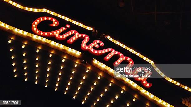 Low Angle View Of Neon Cinema Sign At Night