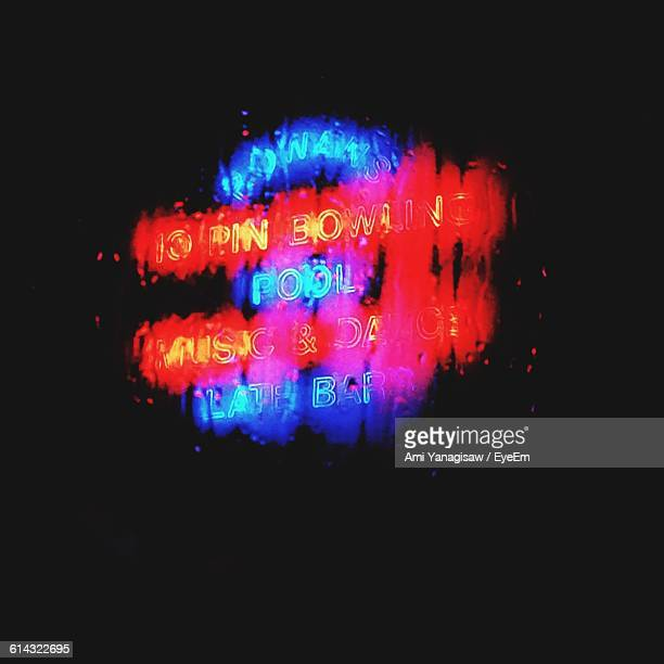 Low Angle View Of Neon Sign Seen Through Wet Window In Rainy Season