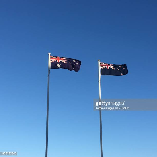 low angle view of new zealand flags waving against clear blue sky - new zealand flag stock photos and pictures