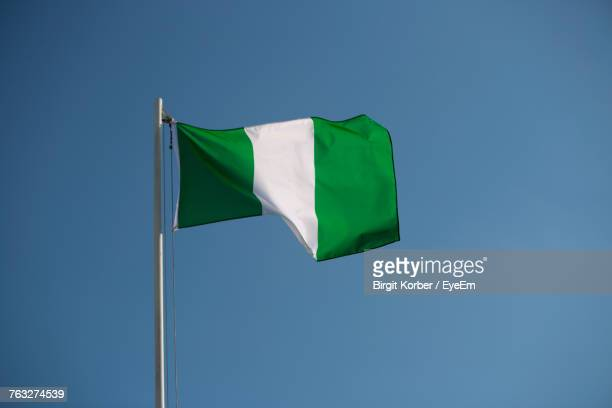 low angle view of nigerian flag against clear blue sky - nigerian flag stock photos and pictures