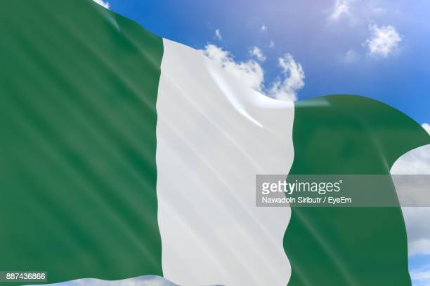 low angle view of nigerian flag against sky - nigerian flag stock photos and pictures
