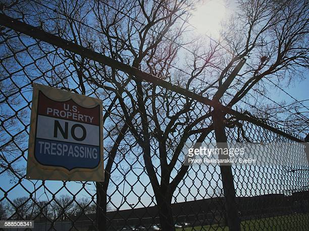 Low Angle View Of No Trespassing Sign On Chainlink Fence Against Sky
