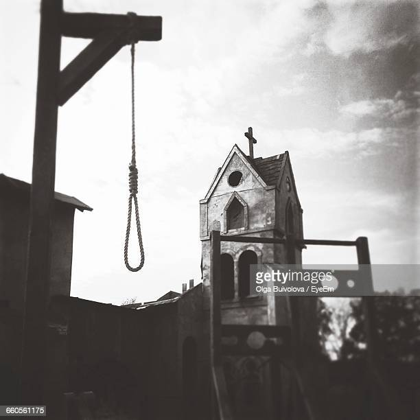 low angle view of noose by old church against sky - execution stock pictures, royalty-free photos & images