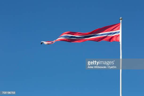 Low Angle View Of Norwegian Flag Fluttering Against Clear Blue Sky