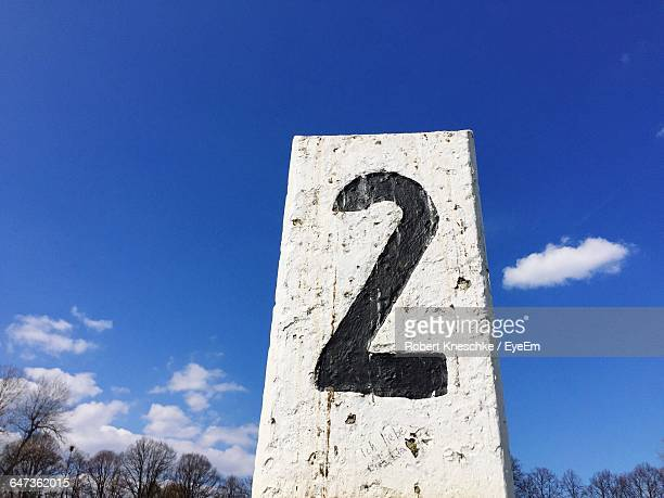 Low Angle View Of Number On Road Marker Against Sky