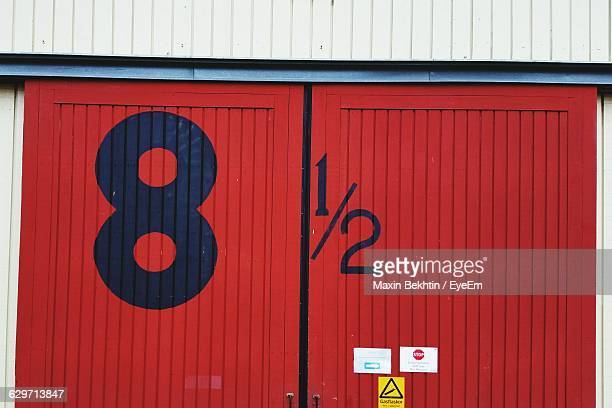 low angle view of numbers on red metallic door - number 8 stock pictures, royalty-free photos & images