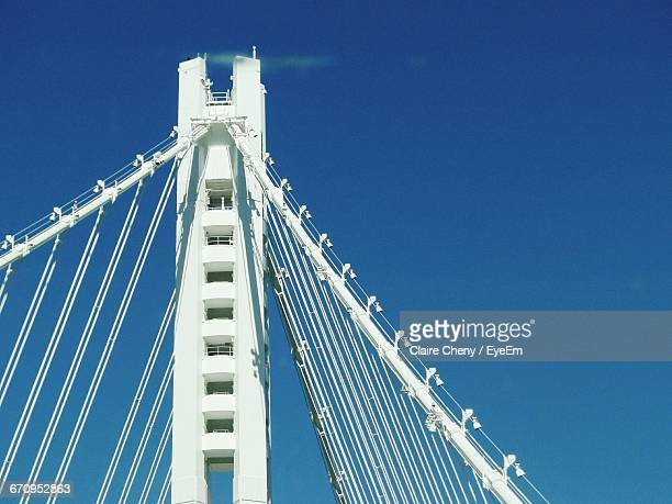 low angle view of oakland bay bridge against sky - bay bridge stock pictures, royalty-free photos & images