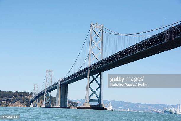 low angle view of oakland bay bridge over river against clear sky - oakland bay bridge stock pictures, royalty-free photos & images