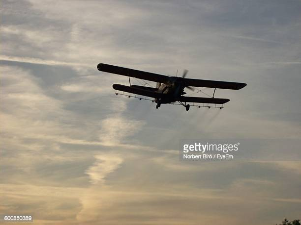 Low Angle View Of Old Airplane Flying Against Sky During Sunset