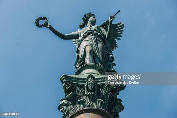 low angle view of old angel statue against blue sky at charlottenburg palace - charlottenburg palace stock pictures, royalty-free photos & images