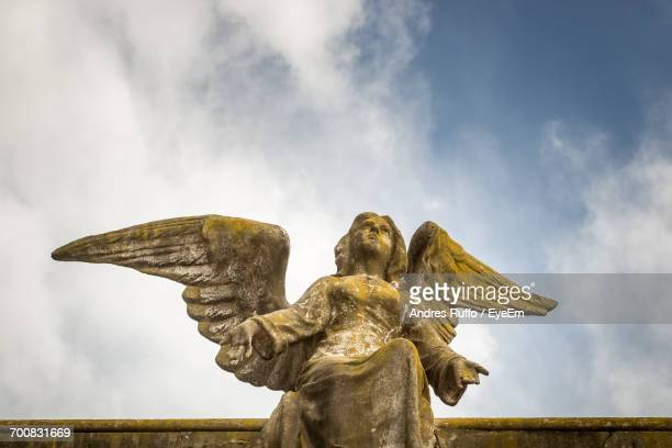 low angle view of old angel statue against sky - andres ruffo stock photos and pictures