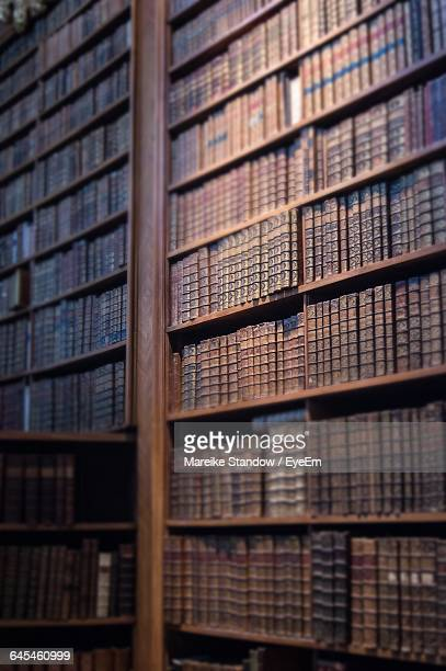 Low Angle View Of Old Book Arranged In Shelf At Library