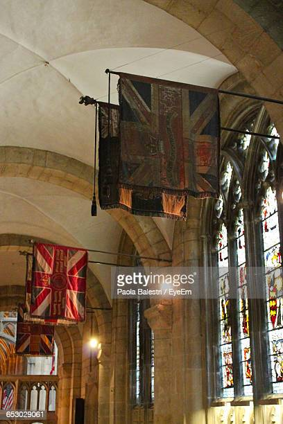 Low Angle View Of Old British Flags At Gloucester Cathedral