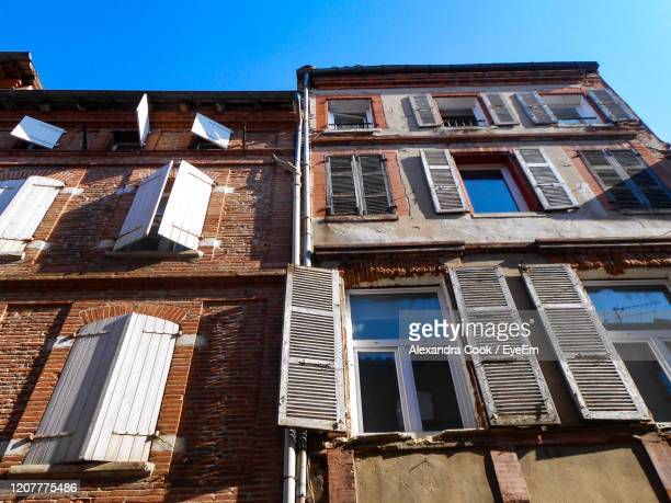 low angle view of old building against blue sky - toulouse stock pictures, royalty-free photos & images