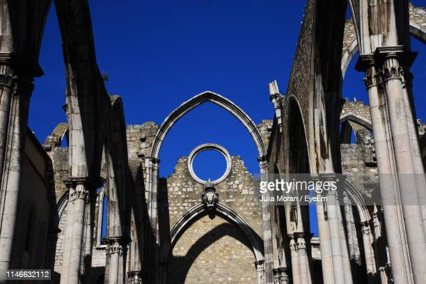 low angle view of old church against clear blue sky - faith moran stock photos and pictures