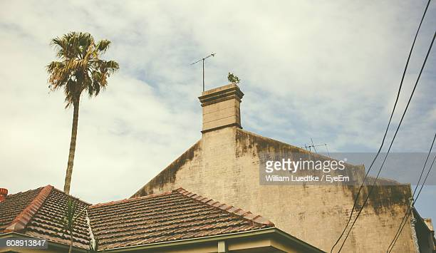 Low Angle View Of Old House By Coconut Palm Tree Against Sky