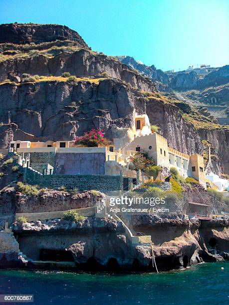 Low Angle View Of Old Houses On Mountain By Sea At Santorini