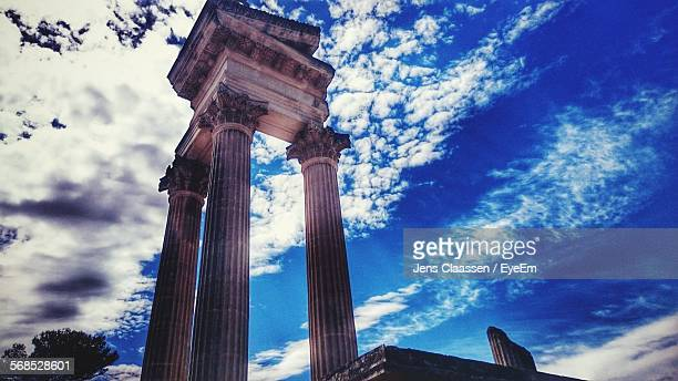 Low Angle View Of Old Ruined Columns Against Cloudy Sky