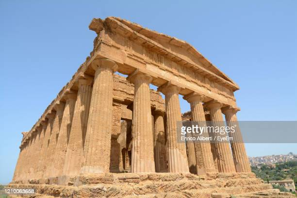 low angle view of old temple against clear sky - enrico aliberti stock-fotos und bilder