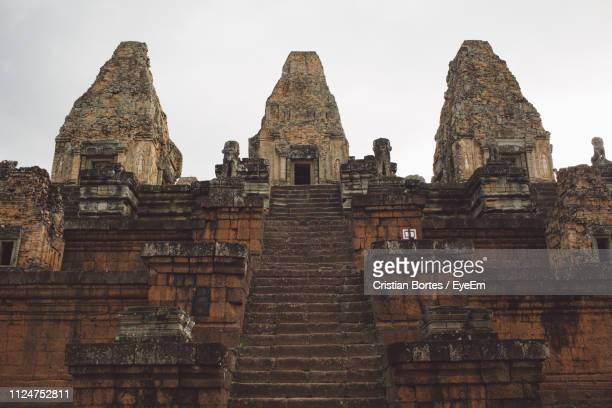 low angle view of old temple building against sky - bortes stock-fotos und bilder
