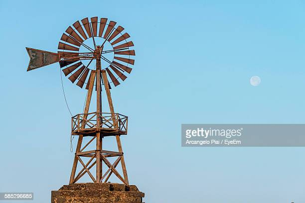 low angle view of old-fashioned wind turbine against clear sky - mill stock pictures, royalty-free photos & images