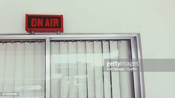 Low Angle View Of On Air Sign Over Window On Wall