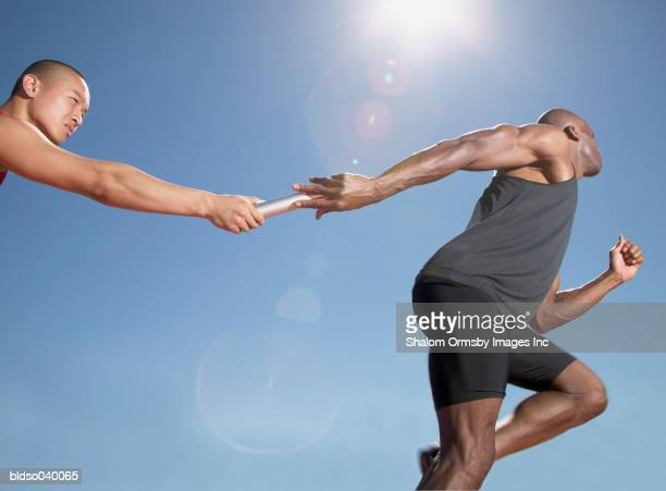 Low angle view of one man passing a baton to another in a relay race