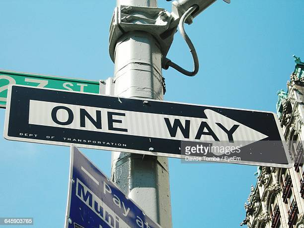 Low Angle View Of One Way Arrow Sign Against Clear Sky