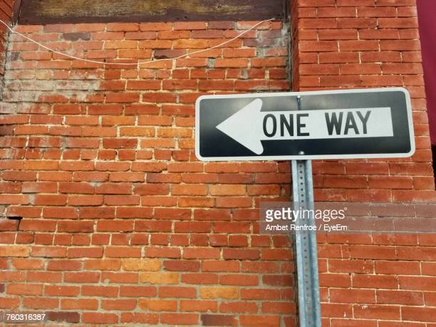 low angle view of one way sign on brick wall - one direction stock pictures, royalty-free photos & images