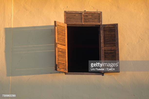Low Angle View Of Open Brown Wooden Window Of House
