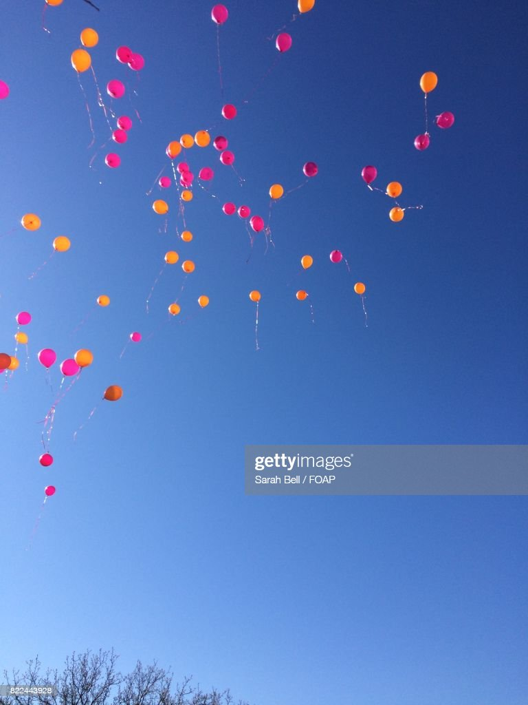 Low angle view of orange and red balloons in sky : Stock Photo